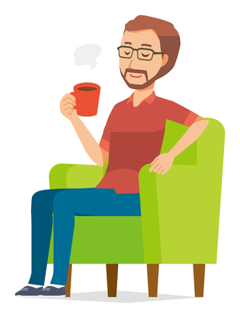 A bearded man wearing eyeglasses is sitting on a sofa and drinking coffee