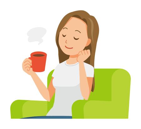 Une jeune femme aux cheveux longs est assise sur un canapé et boit du café
