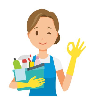 Una donna che indossa un grembiule blu e un guanto di gomma sta suonando un segno ok, tenendo in mano alcuni strumenti per la pulizia