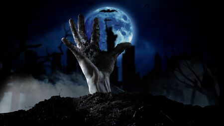 Spooky graveyard with zombie hand coming out of the ground Stockfoto - 132966570