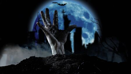 Spooky graveyard with zombie hand coming out of the ground Stockfoto