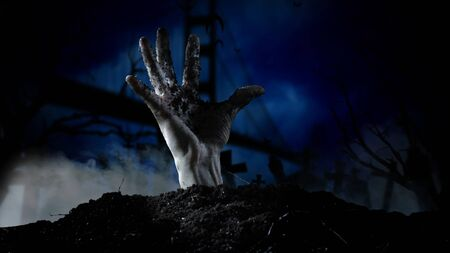 Spooky graveyard with zombie hand coming out of the ground Stock Photo