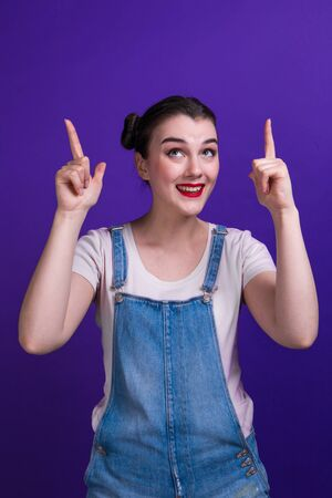 Portrait of a happy young woman pointing fingers up at copy space isolated over purple background
