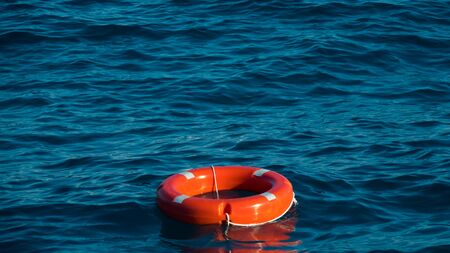 Life buoy or rescue buoy floating on sea to rescue people from drowning man. Safety equipment. Light waves on a sunny day Zdjęcie Seryjne