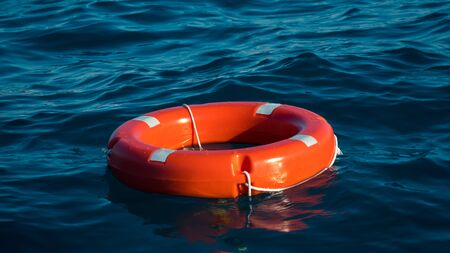 Life buoy or rescue buoy floating on sea to rescue people from drowning man. Safety equipment. Light waves on a sunny day