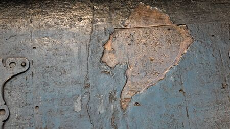 Old wooden wall from which part of the paint has fallen off, close up. Texture of wood background.