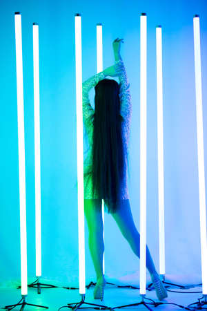 Rear view of a seductive brunette woman with long hair in a short shiny dress stands against a background of neon tubes.
