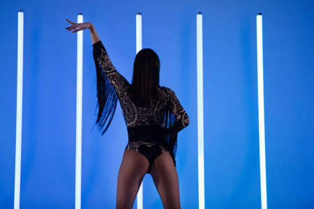 Rear view of a slender woman in a bodysuit with fringes posing with her hand raised elegantly against the background of neon lamps. Stock fotó
