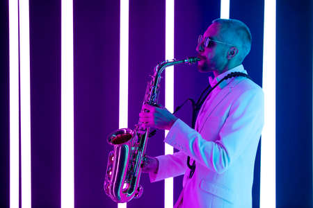 Side view stylish man in a white suit with a bow tie plays the saxophone in the studio. Saxophonist against the background of neon lamps with blue backlight.