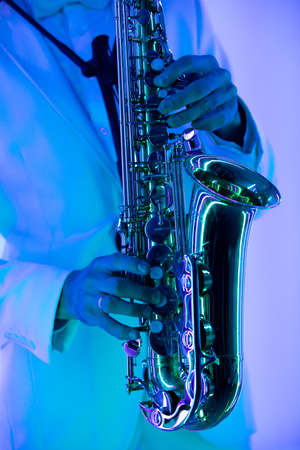 Partial view of stylish professional musician in white suit playing saxophone. Hands and musical instrument close up.