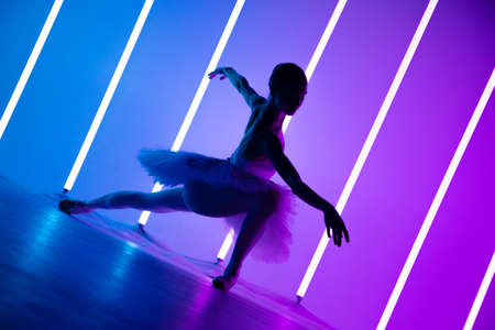 Young graceful ballerina in pointe shoes and a white tutu demonstrates her dancing skills. A beautiful classical ballet dancer against the backdrop of bright neon lights in a dark studio. Silhouette.