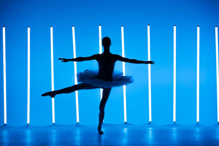 Portrait of a young ballerina on pointe shoes in a white tutu against background of bright blue neon lights. A young graceful ballet dancer in graceful pose. Silhouette. Ballet school poster.