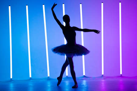 Portrait of a young ballerina on pointe shoes in a white tutu against background of bright neon lights. A young graceful ballet dancer in graceful pose. Silhouette. Ballet school poster.