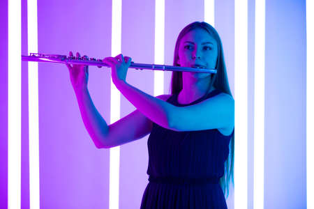 Young pretty woman in black dress plays the flute. Musician female posing in a dark studio against the backdrop of bright neon lights. Close up. Poster for advertising a music school.