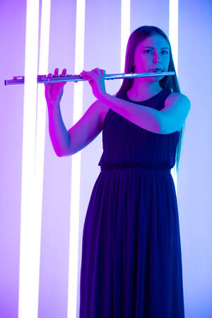 Young pretty woman in black dress plays the flute. Musician female posing in a dark studio against the backdrop of bright neon lights. 写真素材