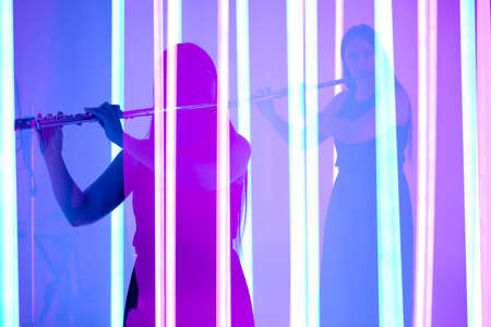 Collage of the shadows of an attractive female musician playing a flute on a wind instrument. A woman plays music against the backdrop of bright neon lights. Silhouette close up. 写真素材