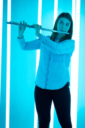 Portrait of a professional flute player playing a wind instrument. Young woman posing in a dark studio against the backdrop of bright neon lights.