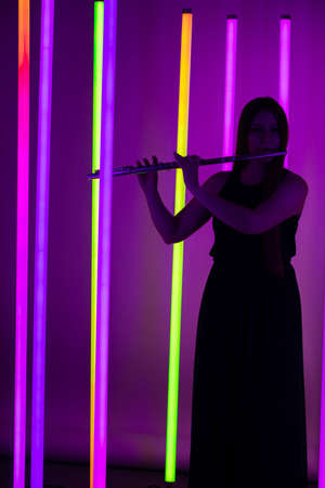Young pretty woman in black dress plays the flute. Musician female posing in a dark studio against the backdrop of bright neon lights. Silhouette.