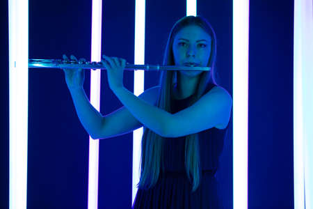 Woman plays the flute. Pretty flute player plays a wind instrument. Beautiful woman model with long hair against a background of bright neon lights. Close up. 写真素材