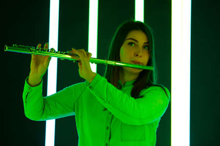 Woman in a white blouse plays the flute against a background of bright neon lights. Cute young female artist with a musical instrument in his hands. Poster for advertising a music school. Close up. 写真素材