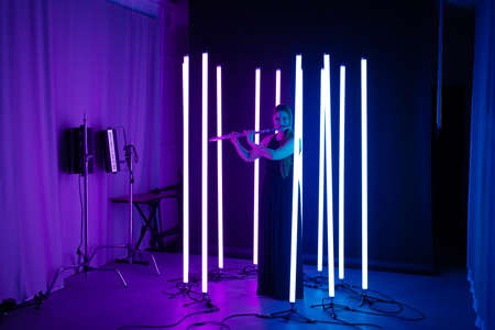 Young pretty woman playing the flute in a dark studio among the bright lights of neon tubes. Musician female in black long dress posing and smiling. 写真素材