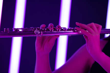 Flute in female hands. Fingers touch flute keys close up. Wind instrument against the background of bright neon lights. Poster for advertising a music school. 写真素材