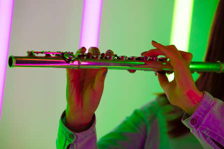 Wind instrument flute close up. Female hands hold a flute against the background of bright neon lights in a dark studio. Poster for advertising a music school. 写真素材