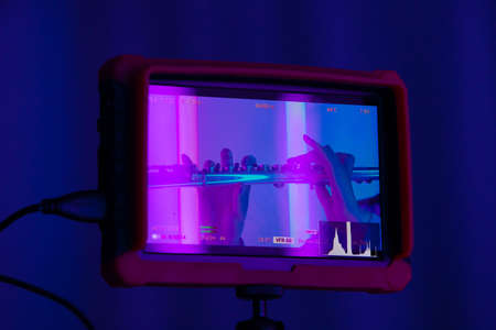 Camcorder display with a flute in female hands. Fingers touch flute keys close up. Wind instrument against the background of bright neon lights.
