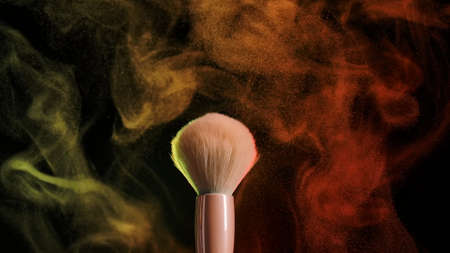 Two makeup brushes, touching each other, form a beautiful multicolored vortex of particles of cosmetic powder. Close up of makeup brushes in dark studio in neon light. Slow motion.