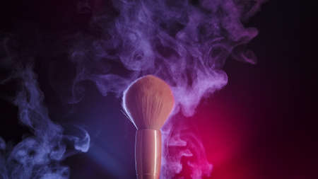 Two makeup brushes touch each other to form an intricate swirl of cosmetic powder particles. Close up of makeup brushes in a dark studio in bright neon light. Slow motion.