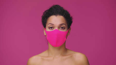Beauty portrait of young African American woman in pink protective pitta mask looking at camera. Black female nude model posing on pink studio background. 스톡 콘텐츠