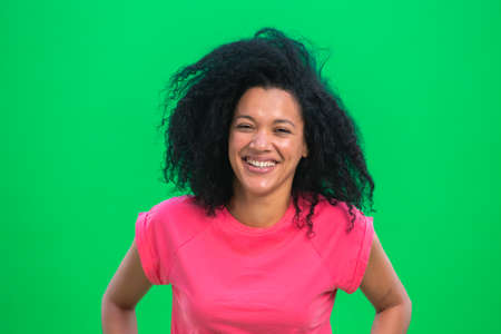 Portrait of young female African American laughing happily. Black woman with curly hair in pink tshirt poses on green screen in the studio. Close up.