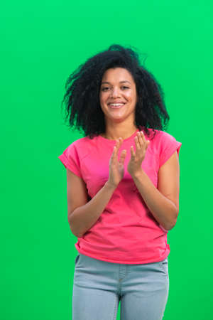 Portrait of young female African American looking at camera and clapping her hands happily. Black woman with curly hair in pink tshirt poses on green screen in studio. Close up.