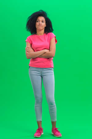 Portrait of young female African American thinking about something, upset that there is no idea. Black woman with curly hair in pink tshirt and jeans poses on green screen in the studio. Full length. 스톡 콘텐츠