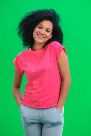 Portrait of young female African American smiling happily. Black woman with curly hair in pink tshirt poses on green screen in the studio. Close up. 스톡 콘텐츠
