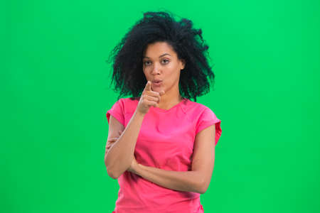Portrait of young female African American pointing at the camera with your index finger. Black woman with curly hair in pink tshirt poses on green screen in the studio. Close up.
