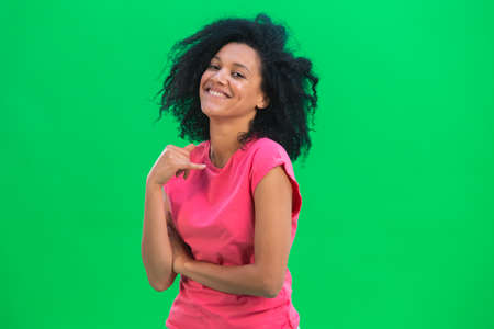 Portrait of young female African American flirtatious smiling. Black woman with curly hair in pink tshirt poses on green screen in the studio. Close up. 스톡 콘텐츠