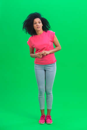 Portrait of young female African American looking around in surprise. Black woman with curly hair in pink tshirt and jeans poses on green screen in the studio. Full length.