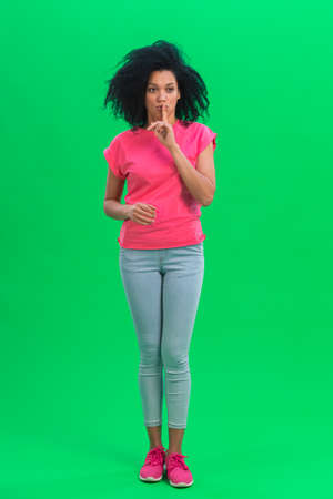 Portrait of young female African American covering her mouth with her hand and whispering the secret and making a hush gesture. Black woman poses on green screen in the studio. Full length.