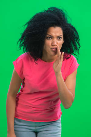 Portrait of young female African American covering her mouth with her hand and whispering the secret. Black woman with curly hair in pink tshirt poses on green screen in studio. Close up. 스톡 콘텐츠