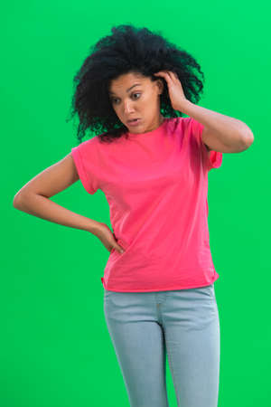 Portrait of young female African American angry and very upset. Black woman with curly hair in pink tshirt poses on green screen in the studio. Close up. 스톡 콘텐츠