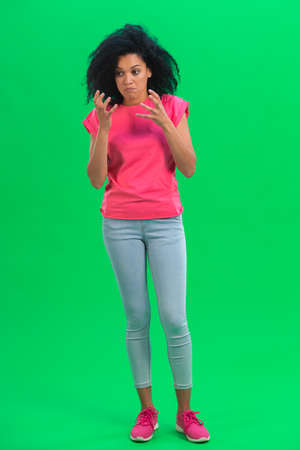 Portrait of young female African American angry and very upset. Black woman with curly hair in pink tshirt poses on green screen in the studio. Full length. 스톡 콘텐츠