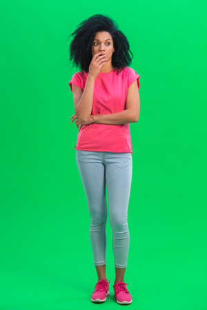 Portrait of young female African American looks frightened to the side. Black woman with curly hair in pink tshirt and jeans poses on green screen in the studio. Full length. 스톡 콘텐츠