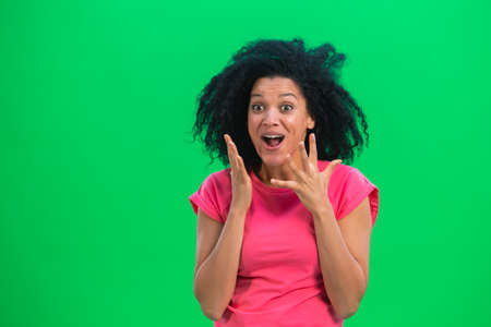 Portrait of young female African American looking at the camera with wow delight and joy. Black woman with curly hair in pink tshirt poses on green screen in the studio. Close up.