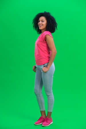Portrait of young female African American smiling happily. Black woman with curly hair in pink tshirt and jeans poses on green screen in the studio. Full length. 스톡 콘텐츠