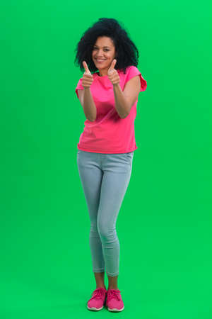Portrait of young female African American showing thumbs up and smiling. Black woman with curly hair in pink tshirt and jeans poses on green screen in the studio. Full length.