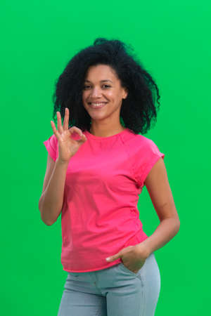 Portrait of young female African American smiling and making sign ok. Black woman with curly hair in pink tshirt poses on green screen in the studio. Close up.