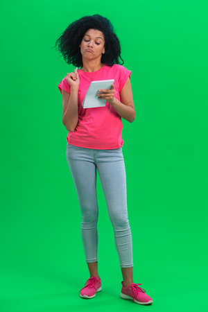 Portrait of young female African American thinking with pen and notebook. Black woman with curly hair poses on green screen in the studio. Full length. 스톡 콘텐츠