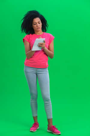 Portrait of young female African American thinking, then happy writing with pen in notebook. Black woman with curly hair poses on green screen in the studio. Full length. 스톡 콘텐츠