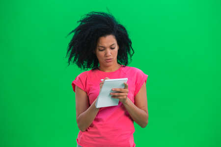 Portrait of young female African American thinking, then happy writing with pen in notebook. Black woman with curly hair poses on green screen in the studio. Close up.